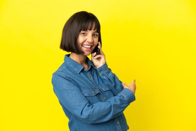 다시 가리키는 노란색 배경에 고립 된 휴대 전화를 사용 하 여 임신한 여자