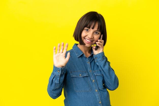 Беременная женщина с помощью мобильного телефона изолирована на желтом фоне, салютуя рукой с счастливым выражением лица