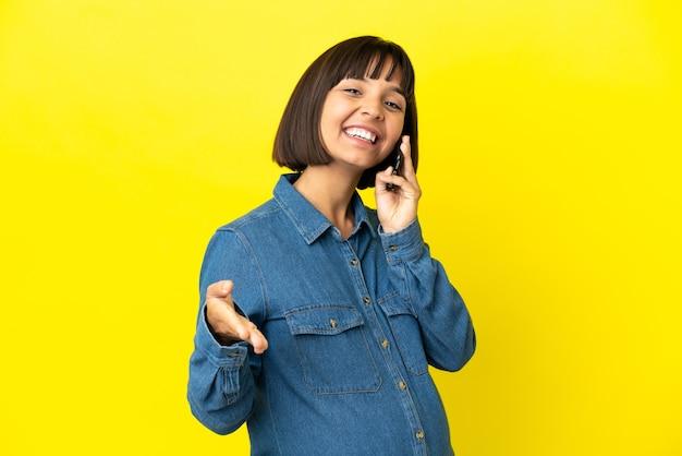 노란색 배경에 격리된 휴대전화를 사용하여 좋은 거래를 성사시키기 위해 악수하는 임산부