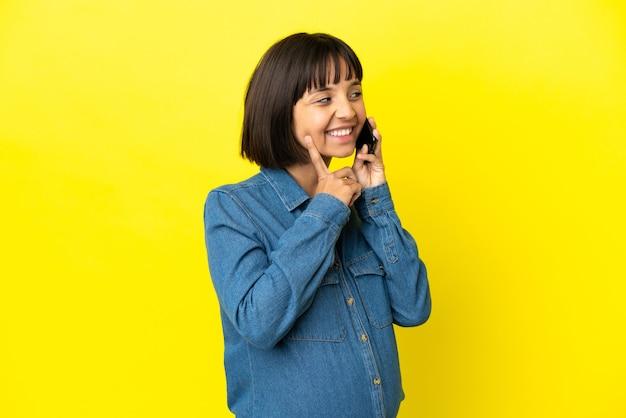 찾는 동안 아이디어를 생각하는 노란색 배경에 고립 된 휴대 전화를 사용하는 임신 한 여자