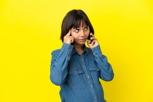 아이디어를 생각하는 노란색 배경에 고립 된 휴대 전화를 사용 하여 임신 한 여자