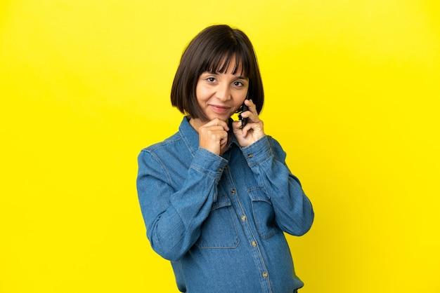 노란색 배경 생각에 고립 된 휴대 전화를 사용 하 여 임신한 여자
