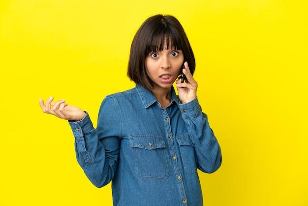ショックを受けた顔の表情で黄色の背景に分離された携帯電話を使用して妊娠中の女性