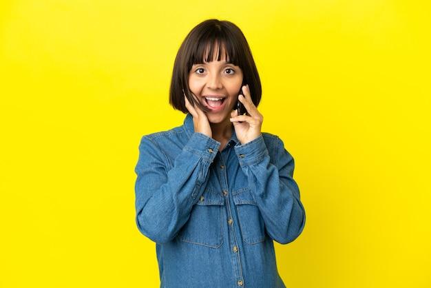 驚きとショックを受けた表情で黄色の背景に分離された携帯電話を使用して妊娠中の女性