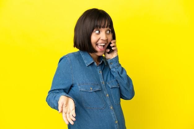 Беременная женщина с помощью мобильного телефона изолирована на желтом фоне с удивленным выражением лица, глядя в сторону