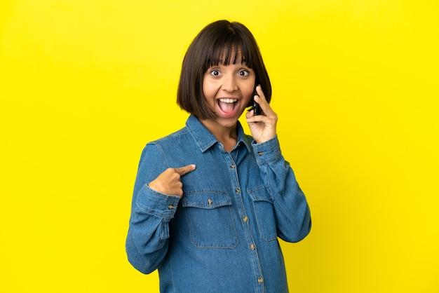 驚きの表情で黄色の背景に分離された携帯電話を使用して妊娠中の女性