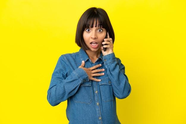 黄色い表面に隔離された携帯電話を使用している妊婦は、右を見ながら驚いてショックを受けました