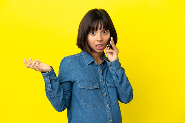 Pregnant woman using mobile phone isolated on yellow background with shocked facial expression