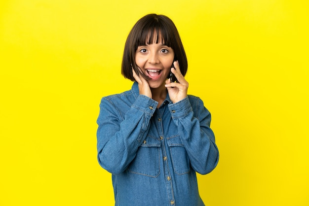 Pregnant woman using mobile phone isolated on yellow background with surprise and shocked facial expression