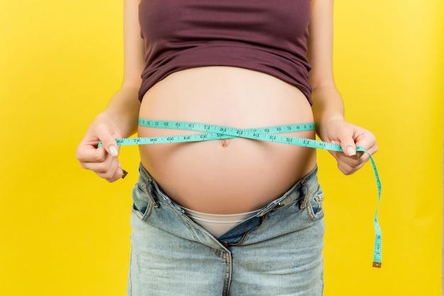 아기를 확인하기 위해 줄자를 사용하여 임신 한 여자
