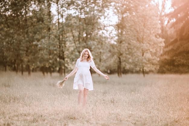 晴れた日に背の高い草の上を歩く妊婦