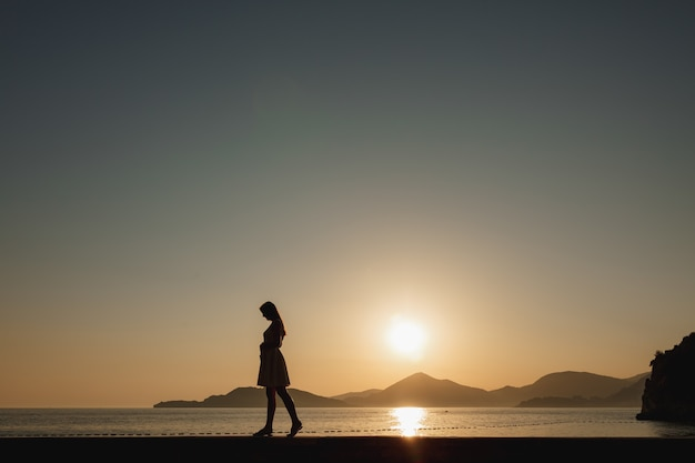 A pregnant woman walks on the seashore at sunset and gently strokes her belly, behind her are mountains and the setting sun .