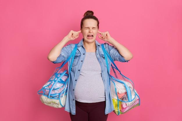 Беременная женщина в повседневной одежде закрывает оба уха пальцами, изолированными на розовом