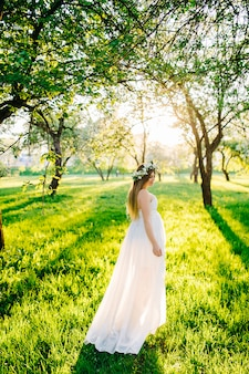 A pregnant woman in a white dress and a floral wreath on her head walking in the garden in the sun. pregnant woman in a flowering botanical garden near blooming sakura.