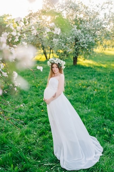 A pregnant woman in a white dress and a floral wreath. pregnant woman in a flowering botanical garden near blooming sakura and apple trees.