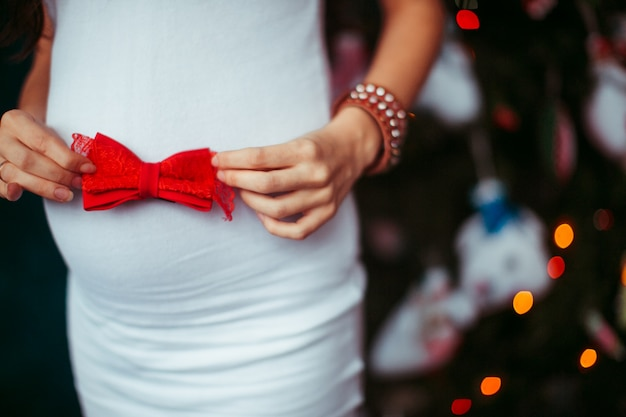 Pregnant woman in white dress holds red bow on her belly