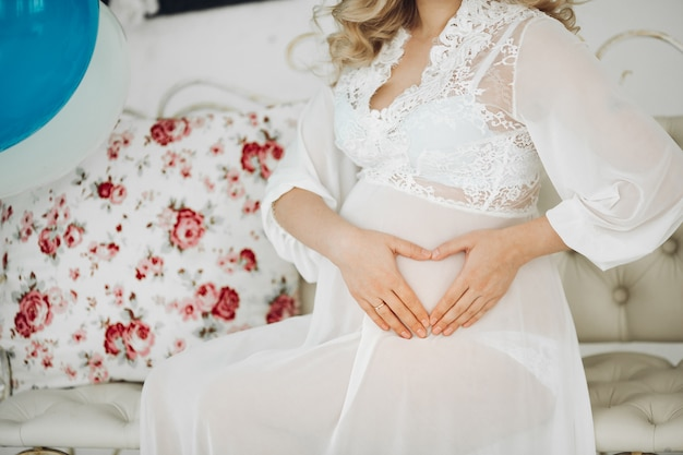 Pregnant woman in white holding hands