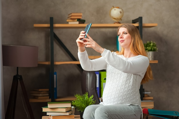Pregnant woman in a white sweater. pregnant blogger takes selfie on the phone.