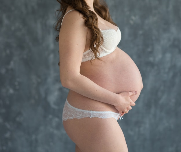Pregnant woman in white underwear hugs belly