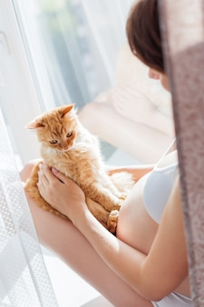 Pregnant woman in white underwear with cute ginger cat
