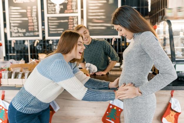 母親に良い知らせを友人に伝えた妊娠中の女性、嬉しそうに反応するガールフレンドが腹に触れます。