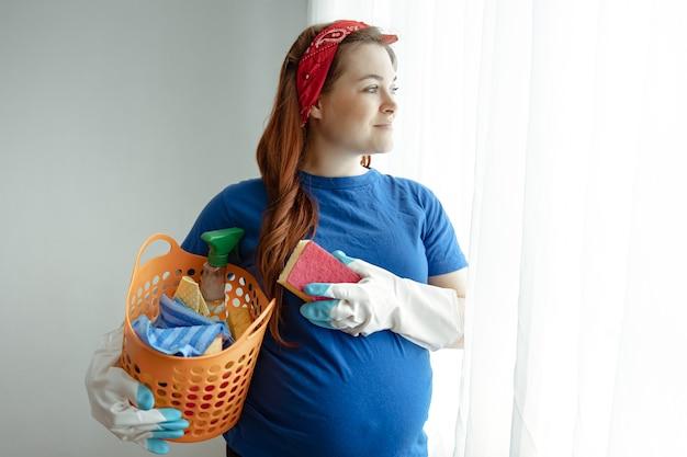 家を掃除して清潔を保つための製品のバスケットを持つ妊娠中の女性。