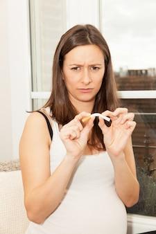 タバコを持つ妊娠中の女性