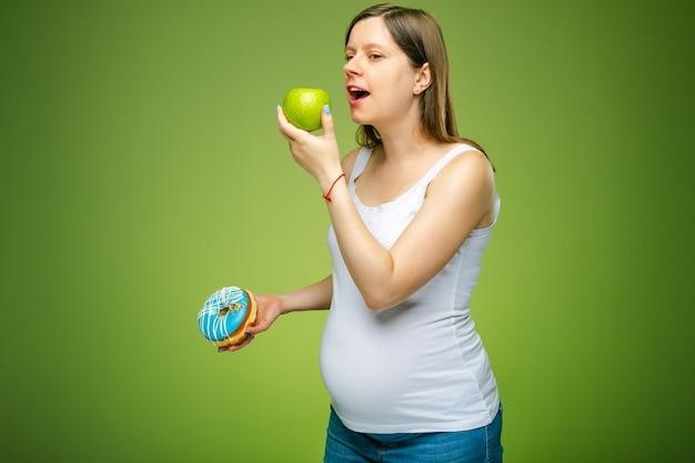 ドーナツと青リンゴを持った妊婦が健康的に食べるべき製品をアドバイス