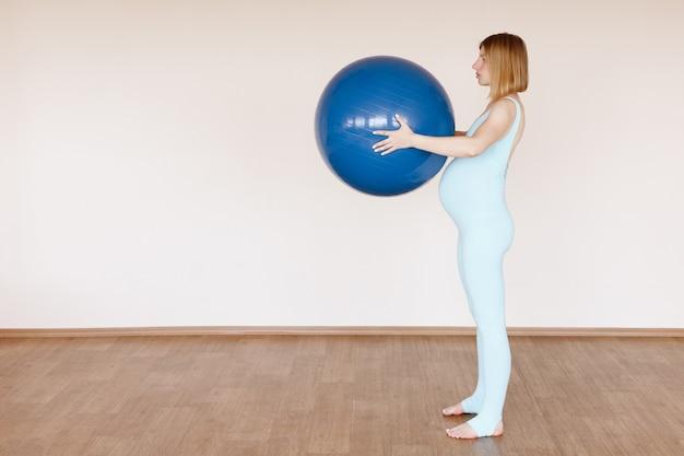 トレーニングで明るいスタジオでフィットネスボールを持つ妊婦
