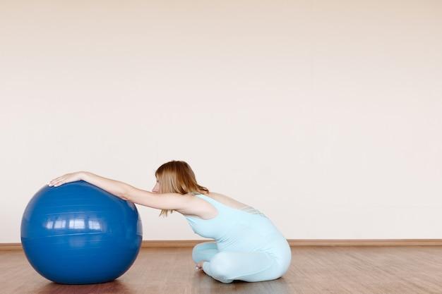 自宅で電車のヨガスーツにフィットネスボールを持った妊婦