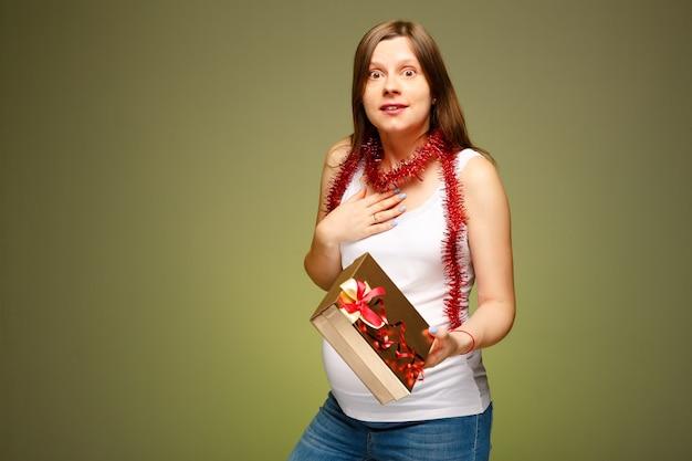 크리스마스 이브에 선물을 받고 놀란 얼굴 표정을 가진 임산부