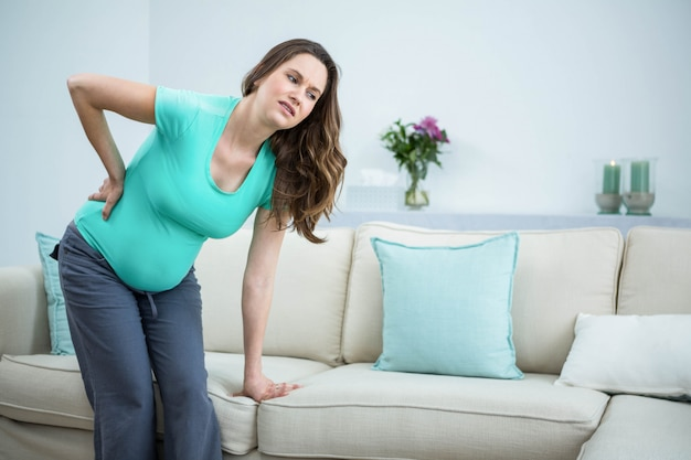 Pregnant woman with back pain in living room