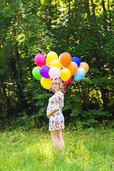 屋外の風船で妊娠中の女性