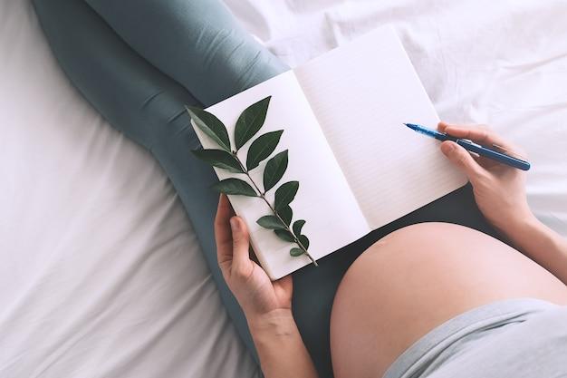 Беременная женщина с красивым животом делает заметки или контрольный список в бумажном дневнике
