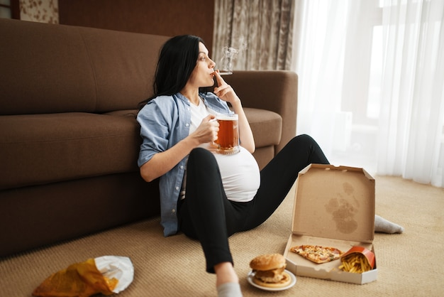 Pregnant woman with belly smoking and drinks beer at home. pregnancy and bad habits, unhealthy lifestyle in prenatal period. ugly expectant mom, health damage, alcoholism