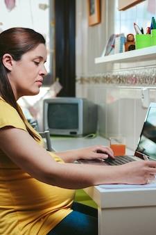Беременная женщина в повседневной одежде работает дома с ноутбуком