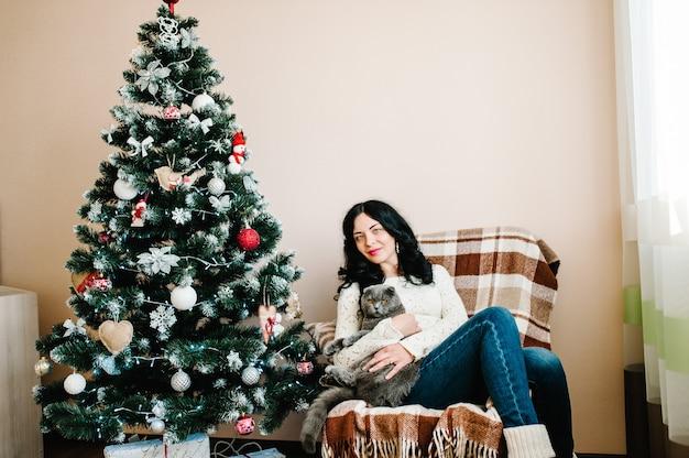 Беременная женщина с кошкой позирует возле елки дома с рождеством и счастливыми праздниками