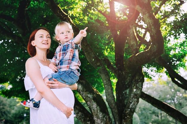 屋外で子供を持つ妊娠中の女性夏の公園で自然の背景に母と息子