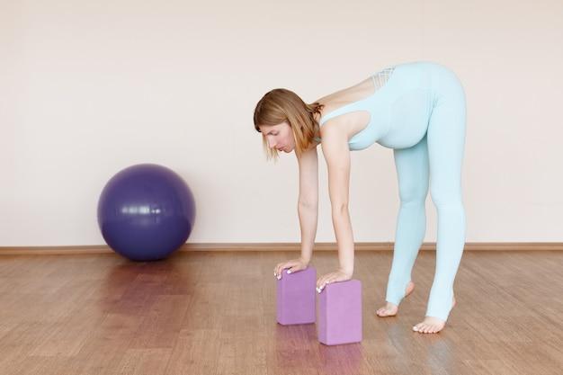 スポーツ用のキューブとボールを持つ妊婦がスタジオに従事しています
