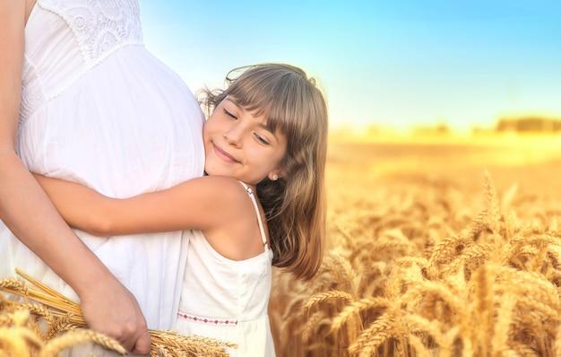 Беременная женщина с дочерью в пшеничном поле