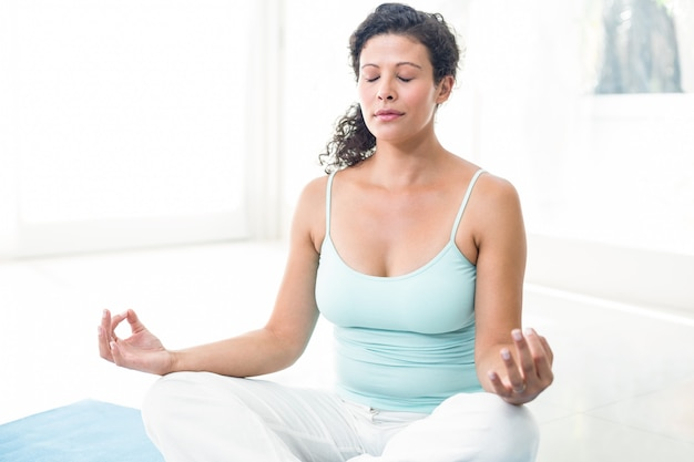 Pregnant woman with eyes closed meditating in lotus position at home