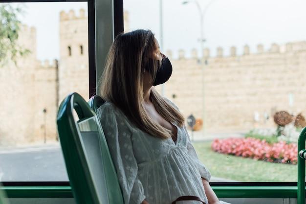 도시 버스 여행을 만드는 얼굴 마스크와 임신 한 여자.