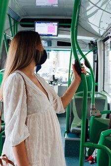 도시 버스를 타고 얼굴 마스크 서 임신 한 여자.