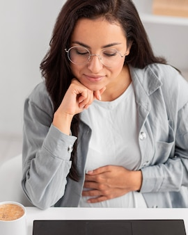 Pregnant woman with glasses working on laptop from home