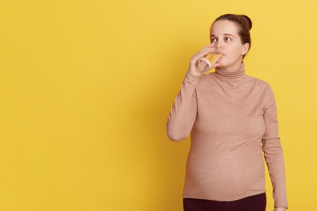 Pregnant woman with hair bun drinking fresh water, looking away isolated over yellow wall.