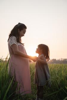 Беременная женщина с дочерью на открытом воздухе