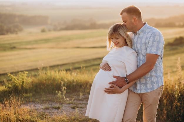 Беременная женщина с мужем в парке