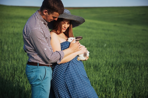 Pregnant woman with her husband and rabbit