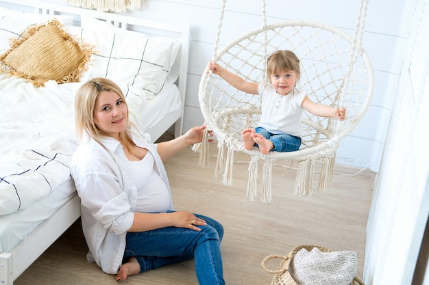 A pregnant woman with her little daughter. baby swinging in a hanging chair, mom sitting on the floor.