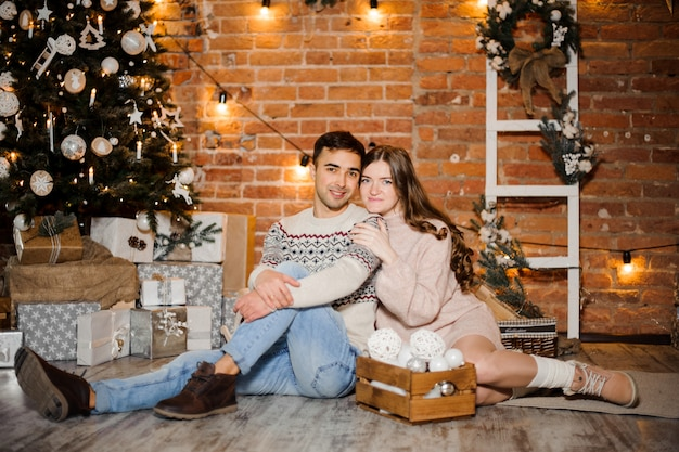 Pregnant woman with husband sitting near the christmas tree and gift boxes